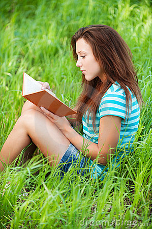 Young woman sits on grass