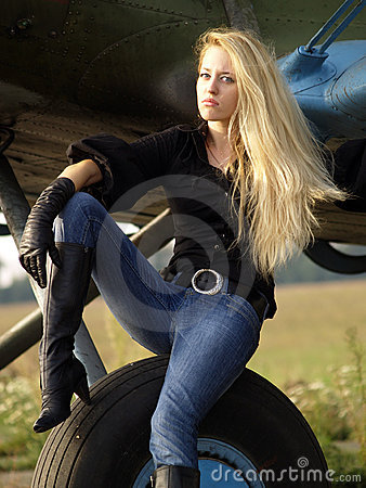 Young woman sitting on airplane landing gear
