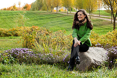 Young woman sitting  in autumn park