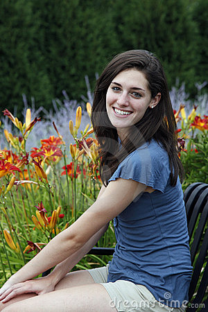 Young woman sitting on a bench with flowers