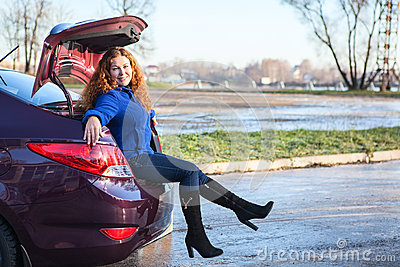 Young woman sitting in car trunk