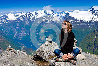 Young woman sitting on cliff and enjoy the view