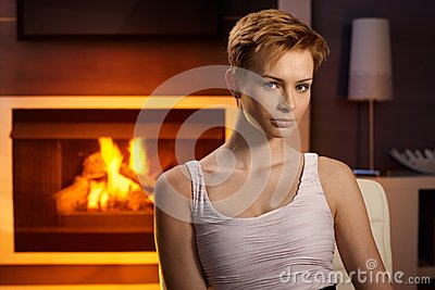 Young woman sitting by fireplace