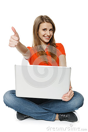 Woman sitting on the floor with her laptop making thumb up