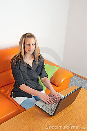 Young woman sitting at home using a laptop