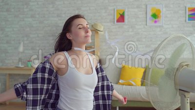 Young woman sitting in living room with electric fan. Enjoying cool wind stock video