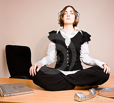Young woman sitting in lotus pose with headphones