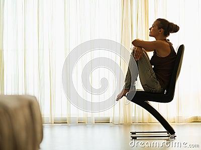 Young woman sitting on modern chair near window