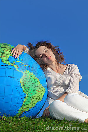 Young woman sitting near big globe Stock Photo