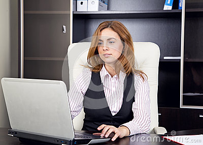 Young woman sitting in office typing on laptop