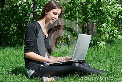 Young woman sitting in park and using laptop