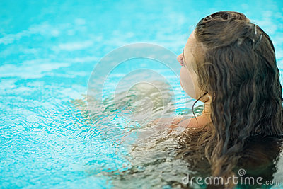 Young woman sitting in pool . rear view