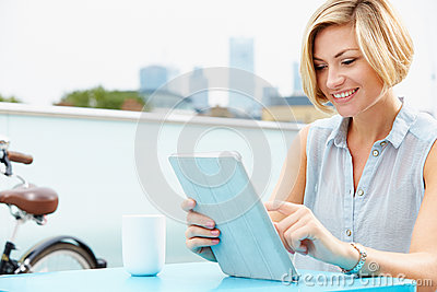 Young Woman Sitting On Roof Terrace Using Digital Tablet