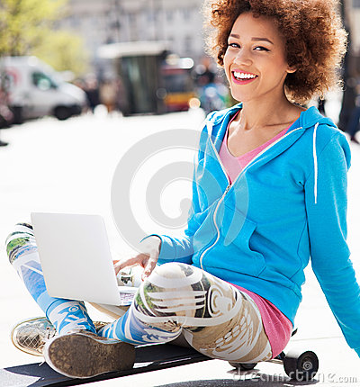 Young woman sitting on skateboard with laptop