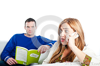 Young woman sitting on sofa at home, talking on a mobile whilst her boyfriend reads