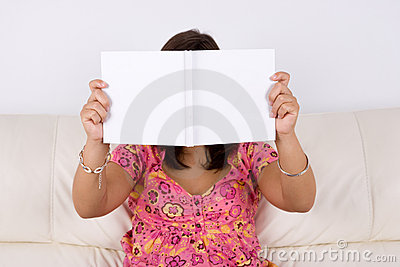 Young woman sitting in the sofa reading white book