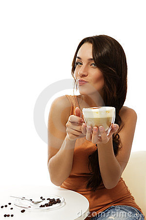 Young woman sitting at a table with cappuccino cof