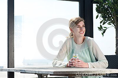 Young woman sitting at a table with a drink at an