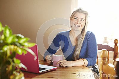 Young woman sitting at table with laptop smiling
