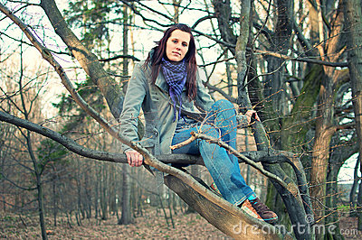 Young woman sitting on tree in the forest