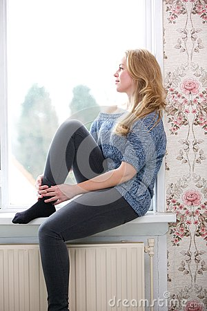 Young woman sitting on windowsill at home
