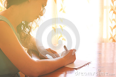 Young woman sitting and writing letter near bright window light. filtered image.