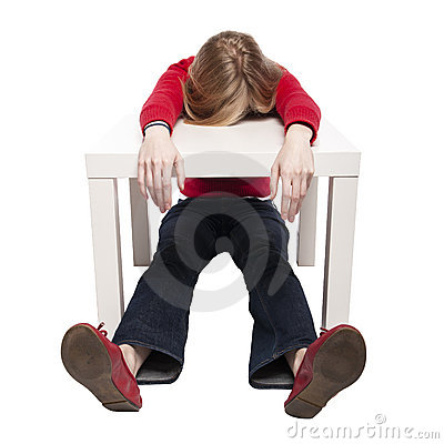 Young woman sleeping at funny small desk