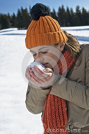 Young woman smelling snow