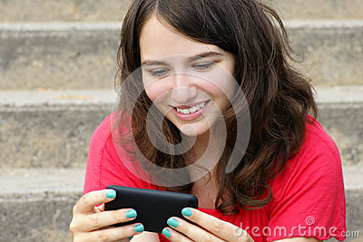 Young woman smiling at cell phone