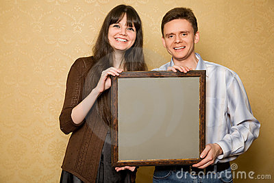Young woman and smiling man with picture in frame