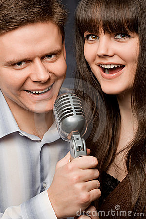 Young woman and smiling man sing in microphone