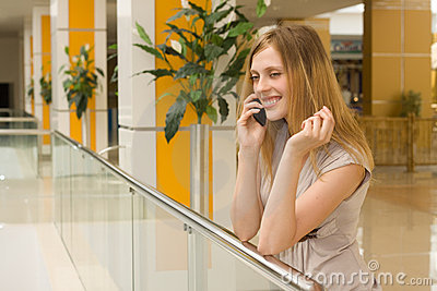 Young woman speaking on cellphone in the mall