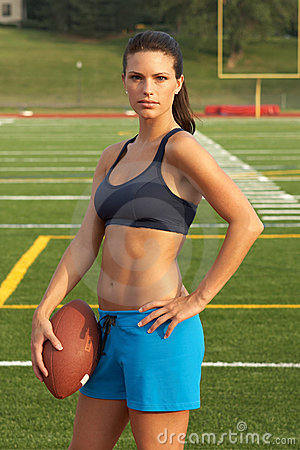 Young Woman in Sports Bra Holding Football with Hand on Hip