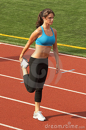 Young Woman in Sports Bra Stretching Quadriceps
