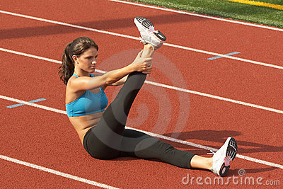 Young Woman in Sports Bra Stretching Raised Leg on Running rack