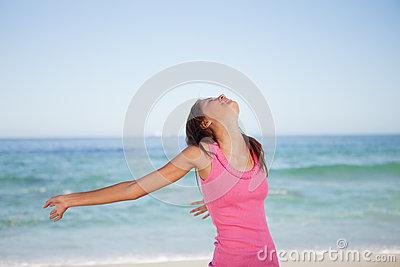 Young woman spreading her arms on the beach