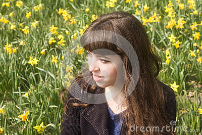 Young woman in spring scene with daffodils
