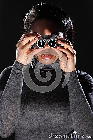 Young woman spy looking through binoculars