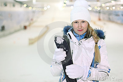 Young woman stand and keeps skis
