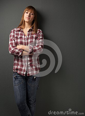 Young woman standing alone with arms crossed