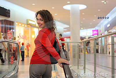 Young woman standing on escalator