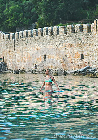 Free Young Woman Standing In Sea At Beach Near Fortress Wall Royalty Free Stock Images - 95397559
