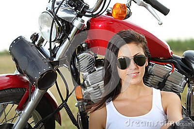 Young woman standing near a motorcycle