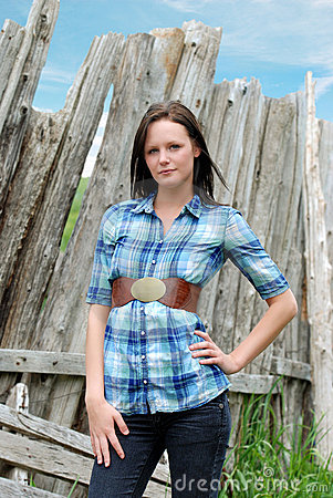 Young woman standing near old wood post fence