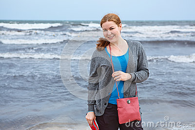 Young woman standing near stormy sea
