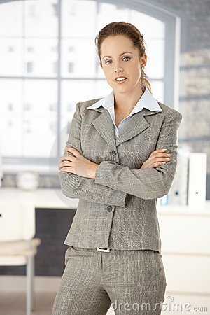 Young woman standing in office arms crossed