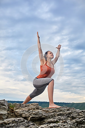 Free Young Woman Standing On The Stone And Practicing Yoga Near The Big River. Stock Photo - 95132190
