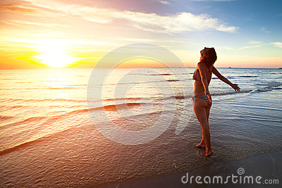 A young woman stands on the beach during a beautiful sunset