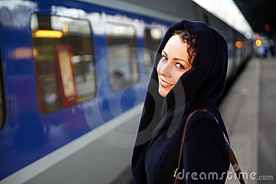 Young woman stands on platform near train