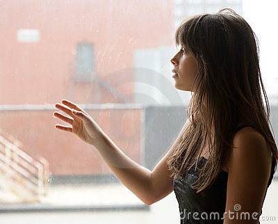 Young Woman Staring Out Large Window